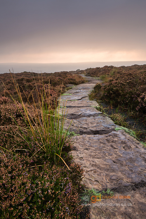 Dawn light adds a welcome touch of colour to the skies above this gently curving paved path on Stanage Edge. A light mist is partially obscuring the distant hills. Autumnal scenes in the Peak District, Derbyshire, England, UK. September, 2014.