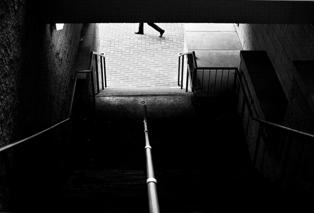 Looking down steps in an urban area at a person walking by, only showing their legs.