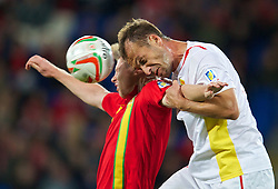 CARDIFF, WALES - Friday, October 11, 2013: Wales' Simon Church in action against Macedonia's Nikolce Noveski during the 2014 FIFA World Cup Brazil Qualifying Group A match at the Cardiff City Stadium. (Pic by David Rawcliffe/Propaganda)