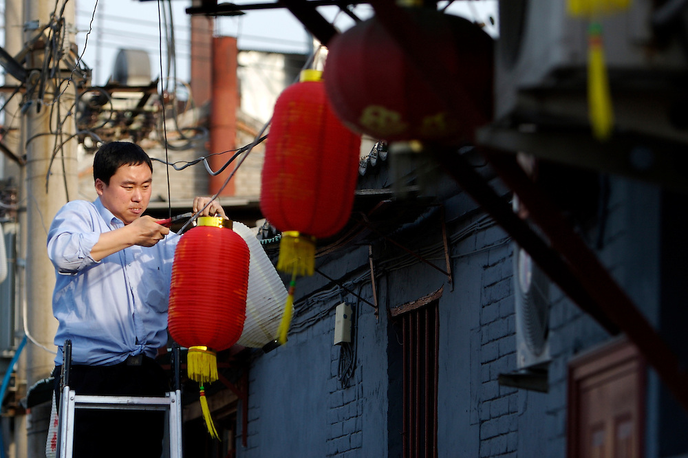 In a small hutong, alleyway, of Shichahai area a man hangs lucky red lanterns in front of a restaurant in Beijing,China.