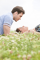 Side view of young man looking at woman sleeping on grass against sky