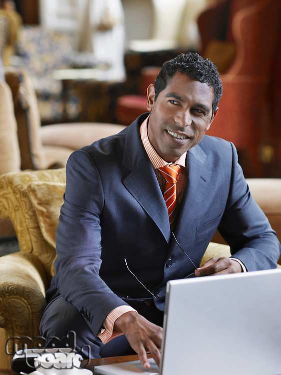 Portrait of business man sitting in lobby working on laptop smiling