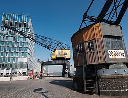 Modern new buildings and old heritage dock crane on riverside at Rheinaufhafen property development in Cologne Germany