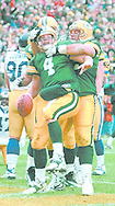 (Published caption 11/10/97) Packers quarterback Brett Favre tries to spike the ball after a 7-yard touchdown run in the fourth quarter. Teammates Mark Chmura, behind, and Frank Winters hold Favre up.