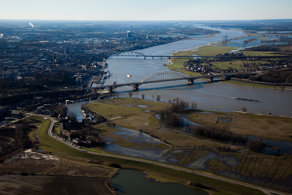 Nederland, Gelderland, Nijmegen, 07-03-2010; Waalsprong: aan de noordoever van de Waal (rechts), rond het dorp Lent, zal een nieuw stadsdeel gebouwd gaan worden. Ook zal er in de toekomst op deze lokatie een geul uitgegraven worden (meer landinwaarts ten opzicht van de rivier), om de rivier meer de ruimte te geven. Lent (aan de dijk) komt dan op een eiland te liggen. In de voorgrond een begin van de Ooijpolder..Waalsprong (Waaljump): on the north bank of the Waal, around the village of Lent, a new city will be built.Furthermore, in the near future a flood channel will be excavated on this location, to provide the river with more space (because of high water / flooding problems). Lent, on the dike, will become an island.luchtfoto (toeslag), aerial photo (additional fee required).foto/photo Siebe Swart