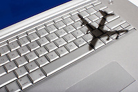 Shadow of jumbo jet over apple macintosh keyboard