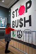 UNITED KINGDOM, London: 21 March 2017 A member of staff at The Imperial War Museum takes a close look at a 'Stop Bush' banner which was made by Ed Hall for a demonstration in London on 20 November 2003, organised by the Stop the War Coalition. The banner forms part of the 'People Power: Fighting for Peace' exhibition at the Imperial War Museum which explores the evolution of the anti-war movement from the First World War to the present day. Rick Findler / Story Picture Agency