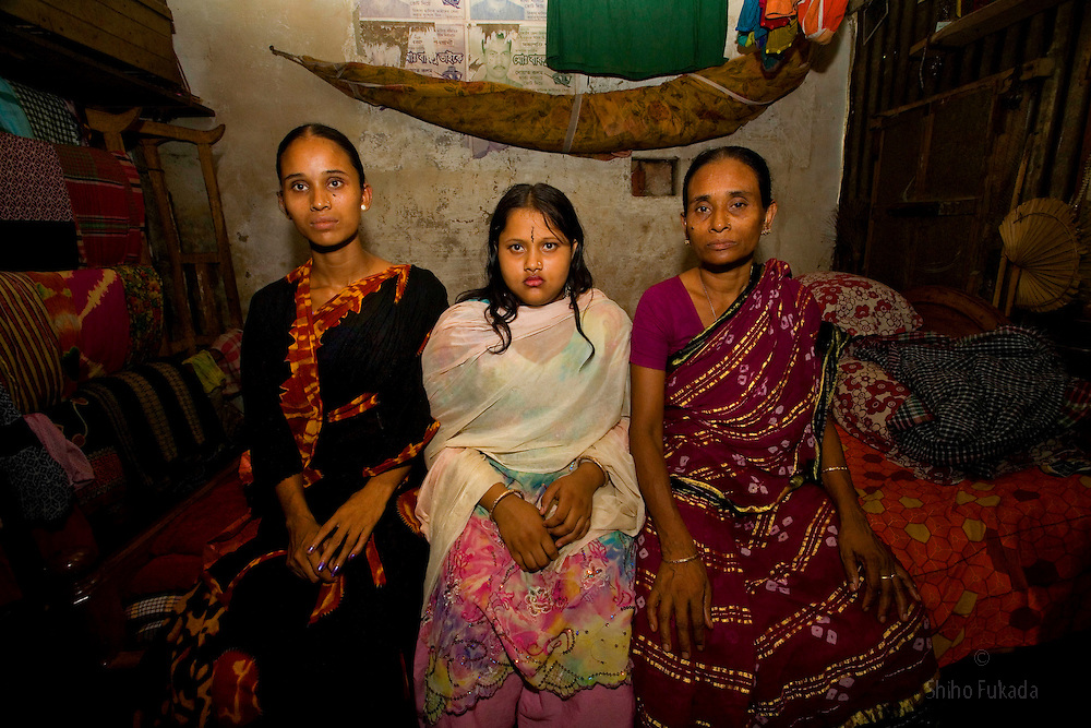 A family of sex workers Munnie, 15, center, mother Mukta, 33, left,  and grandmother Jova, 47, sit for a portrait at brothel in Tangail, Bangladesh. Munnie, 15, was taken out of school to join the family business. Jova, her grandmother, felt there was little choice.