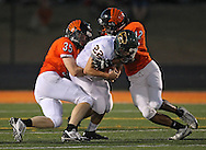 Kennedy's Jay Blank (22) is wrapped up by Prairie's Benjamin Boldt (35) and Marquan Wilder (42) during their game at John Wall Memorial Stadium at Prairie High School in Cedar Rapids on Friday, September 6, 2013.