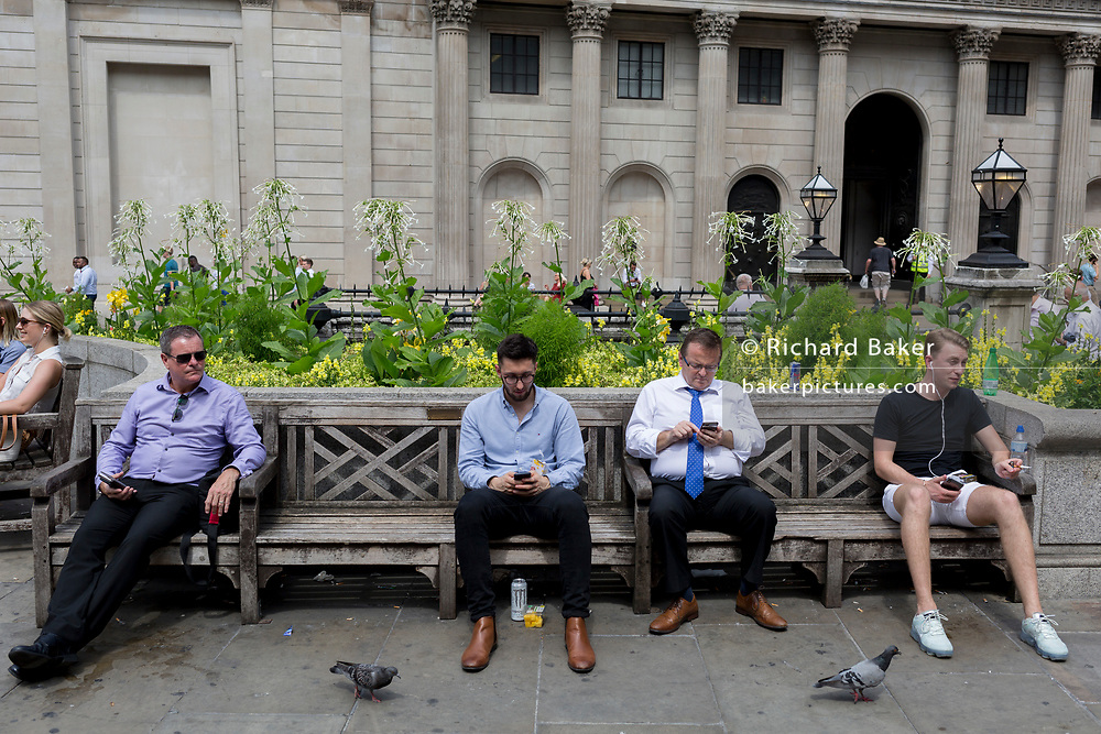 As heatwave temperatures climb to record levels - the hottest day of the year so far - Londoners in the City of London (the capital's financial district aka the Square Mile) rest on benches opposite the Bank of England on Threadneedle Street, on 25th July 2019, in London, England.