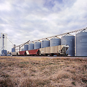 Grain Elevators with railroad siding in Texas under cloudy sky.
