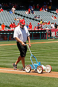 ANAHEIM, CA - JULY 21:  A member of the grounds crew lines the first base line before the Los Angeles Angels of Anaheim game against the Texas Rangers on Saturday, July 21, 2012 at Angel Stadium in Anaheim, California. The Rangers won the game 9-2. (Photo by Paul Spinelli/MLB Photos via Getty Images)