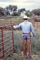 cowboy closing a ranch gate
