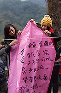 Two women with wishes on a sky lantern. Pingxi Sky Lanterns Release at Jingtong, Taiwan