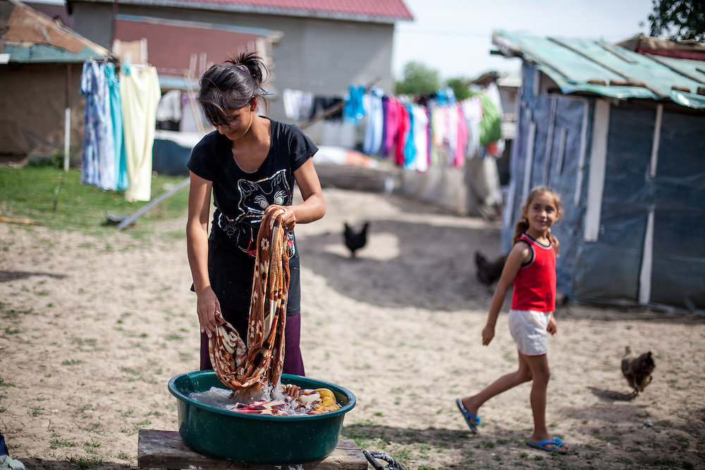 Constantin Ionela Manimar washing clothes for the family by hand and outside because of the lack of electricity in this particular Roma area of Frumusani.
