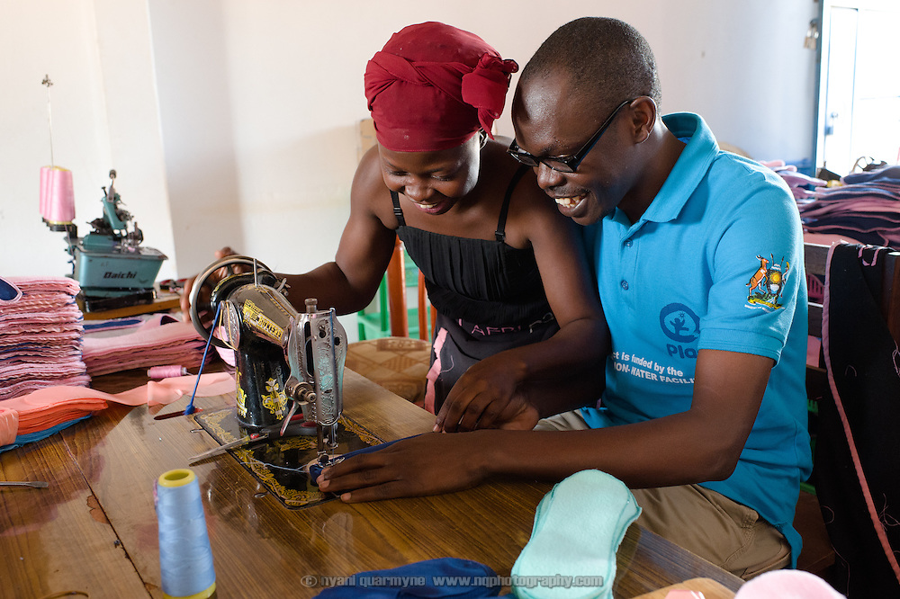 Sylivia Nalule teaching Moses Opolot, Plan Uganda Program Officer for Menstrual Hygiene Management, how to sew a sanitary pad at the Afripads factory in the village of Kitengeesa in the Central Region of Uganda on 30 July 2014.<br /> <br /> Started by volunteers in 2009, Afripads manufactures reusable fibre sanitary pads made locally by community residents. Beginning with a single employee, the company now employs roughly 100 women and produces approximately 700 kits (consisting of pads, holders and a bag) each week. At USh 12,000 to 15,0000 (&pound;2.75 to &pound;3.40) for a kit that lasts approximately one year, Afripads offer a significant saving over disposables which may cost in excess of USh 42,000 (&pound;9.60) over the course of a year. And for the many girls and women who cannot afford disposables, they offer an affordable and more hygienic alternative to rags, cotton wool or toilet paper, all of which are frequently used. At schools where Afripads have been distributed, teachers report that absenteeism has dropped sharply as girls who previously did not have access to proper sanitary pads now no longer stay home when they have their periods.