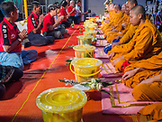 27 JULY 2013 - BANGKOK, THAILAND:  Thai Red Shirts present merit making packages to Buddhist monks during a merit making ceremony to honor Thaksin Shinawatra at a birthday party for Thaksin. The Red Shirts celebrated former Prime Minister Thaksin Shinawatra's 64th birthday with a party at Phibun Prachasan School in Bangkok. They had a Buddhist Merit Making Ceremony, dinner, cake and entertainment. Most of the Red Shirt political elite traveled to Hong Kong for a party with Thaksin. Thaksin, the former Prime Minister, was deposed by a coup in 2006 and subsequently convicted of corruption related crimes. He went into exile rather than go to jail but remains very popular in rural parts of Thailand. His sister, Yingluck Shinawatra is the current Prime Minister and was elected based on her brother's recommendation.    PHOTO BY JACK KURTZ