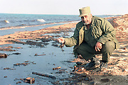 A Qatar coalition officer views a beach covered with crude oil as Iraq dumps oil into the Arabian Sea from the al-Ahmadi terminal January 27, 1991 in al Kafji, Saudi Arabia.