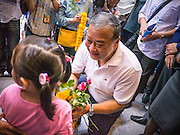 16 JANUARY 2013 - BANGKOK, THAILAND:   SUKHUMBHAND PARIBATRA, candidate for Governor of Bangkok, talks to a child during a campaign walk in downtown Bangkok Wednesday. The Oxford educated Sukhumbhand is a member of the Thai royal family (he is a great grandson of the late Thai King Chulalongkorn). He is a member of the Thai Democrat party and was first elected Governor of Bangkok in 2009. He is running for reelection this year. Sukhumbhand faces six challengers in the March 3 election. His toughest opponent is expected to be Police General Pongsapat Pongcharoen, who is running under the banner of the Pheu Thai Party, which controls the Prime Minister's office and Parliament.   PHOTO BY JACK KURTZ