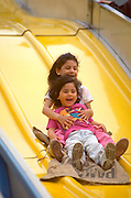 Sisters age 6 and 4 riding fair amusement slide at Cinco De Mayo Celebration.  St Paul  Minnesota USA