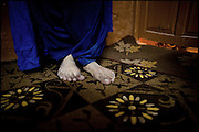 "A detail of the Koumy's feet, a 26 years old transvestite. Koumy wears a typical shalwar kameez and along the sides a dupatta (traditional scarf) goes down. A group of five friends, all transvestites belonging to the medium class, share a common ..apartment where to spend few hours. Late afternoon in south Rawalpindi, Pakistan on Friday, November 28 2008.....""Not men nor women"". Just Hijira, Kusra. Painted lips, Kajal surrounding ..their eyes and colourful veils..Pakistan is today considered a strongly, foundamentalist as well, ..islamic country. But under its reputation, above all over the talebans' ..continuos advancing, stirs a completely extraneous world, a multiethnic ..mixed society. Transvestites make part of it, despite this would not be ..admitted by a strict law..Third gender, the Hijira are born as men (often ermaphrodites) or with ..an ambiguous genital situation, and they have their testicles and penis ..removed through a - often brutal - surgical operation. The peculiarity ..is that this operation does not contemplate the reconstruction of a ..female organ. This is the reason why they are not considered as men nor ..women, just Hijira. They are often discriminated, persecuted  and taxed ..with being men prostitutes in the muslim areas. The members of this ..chast perform dances during celebrations, especially during weddings, ..since it is anciently believed that an EUNUCO's dance and kiss in the ..wedding day brings good luck to the couple's fertility...To protect the identities of the recorded subjects names and specific ..places are fictionals."