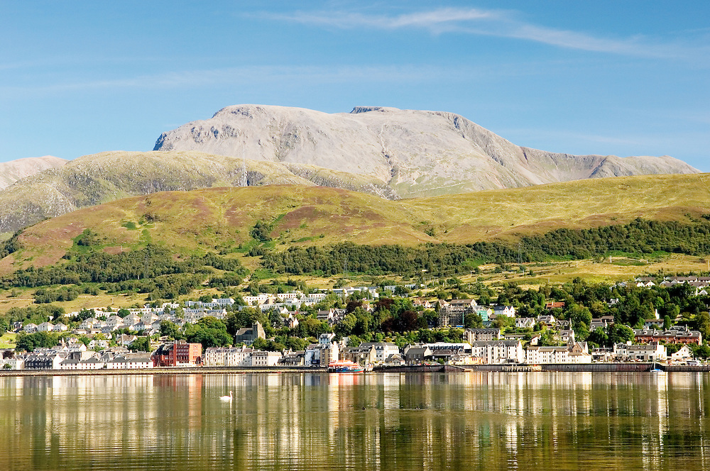 Ben Nevis, highest mountain in UK, rises above Fort William at the head of Loch Linnhe. Western Highlands, Scotland. Summer