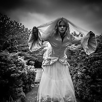 Young blonde female model wearing romantic clothing and veil peering at the camera.