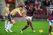 Uche Ikpeazu (#19) of Heart of Midlothian FC runs past Andy Considine (#4) of Aberdeen FC during the Betfred Scottish Football League Cup quarter final match between Heart of Midlothian FC and Aberdeen FC at Tynecastle Stadium, Edinburgh, Scotland on 25 September 2019.