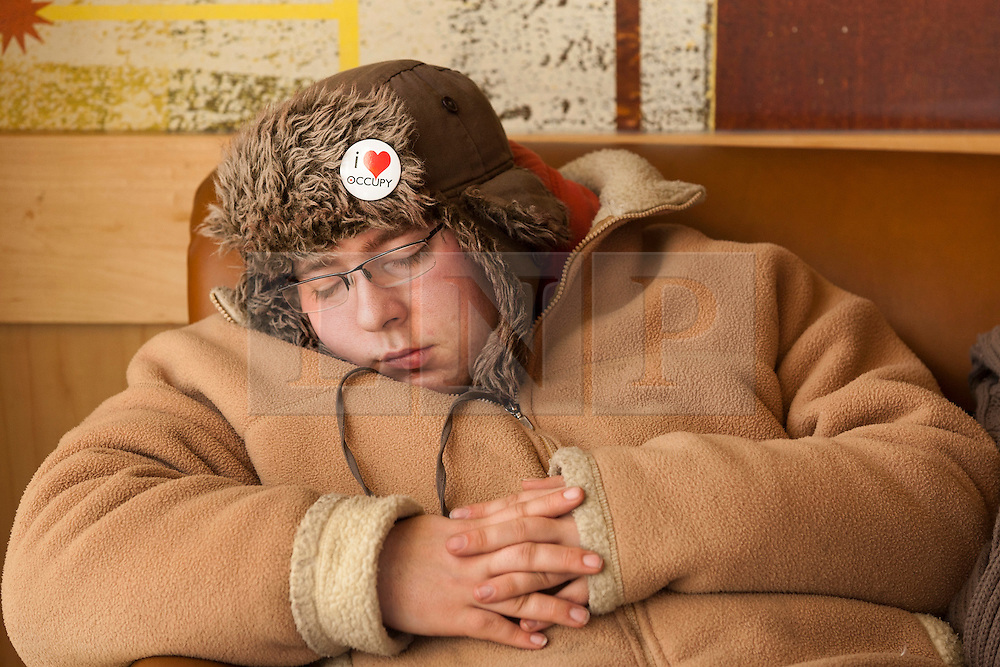 © Licensed to London News Pictures. 25/02/2012. LONDON, UK. Waiting game: An Occupy London supporter snoozes in a nearby coffee house in London. Occupy London protesters carried on with their demonstration today (25/02/12), though waiting for eviction after losing a court battle for the right to keep their St Paul's Cathedral campsite. Photo credit: Matt Cetti-Roberts/LNP