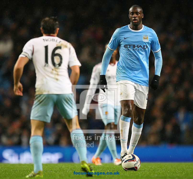 Picture by Paul Chesterton/Focus Images Ltd +44 7904 640267<br /> 08/01/2014<br /> Yaya Tour&eacute; of Man City takes on Mark Noble of West Ham during the Capital One Cup Semi Final 1st Leg match at the Etihad Stadium, Manchester.