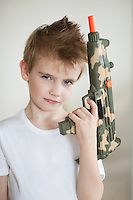 Side view of a young boy holding toy gun