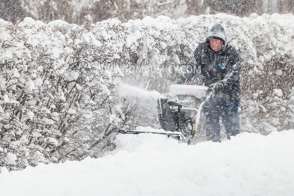 Middletown, New York - A man clears snow from a sidewalk during a snowstorm on Feb. 9, 2017.