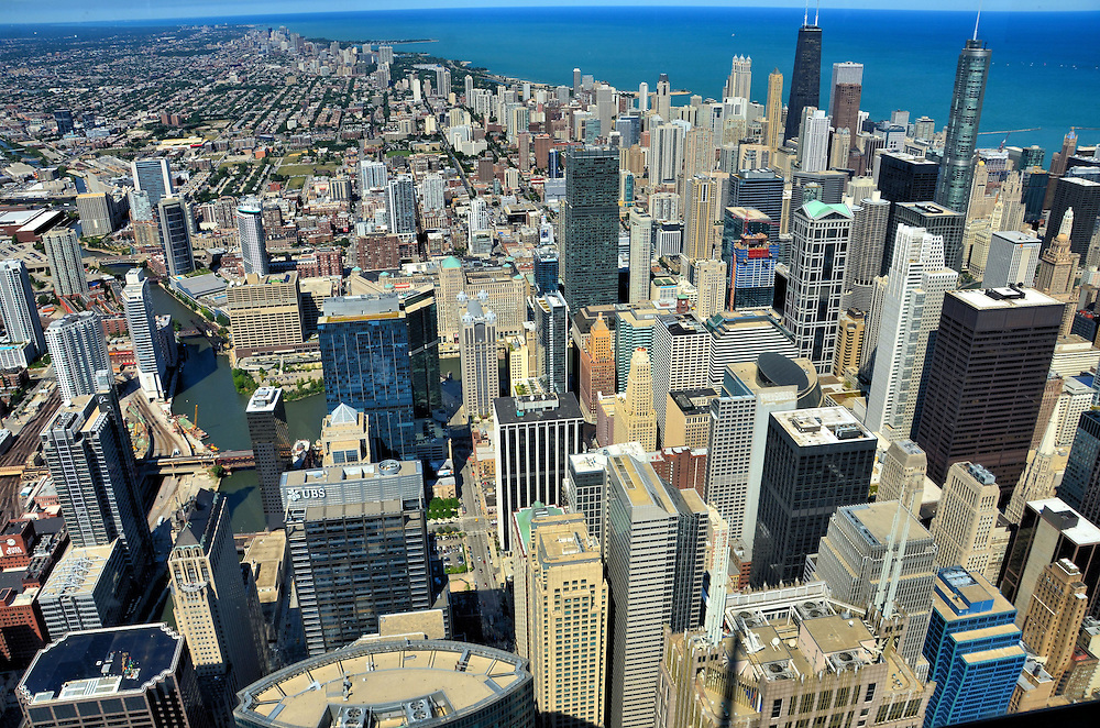 Downtown Chicago Aerial View from Willis Tower in Chicago, Illinois<br /> Formerly named the Sears Tower, the Willis Tower soars 1,451 feet over the Chicago Loop&rsquo;s west side and was the tallest building in the world for 25 years after its completion in 1973.   The Skydeck on the 103rd floor provides over one million visitors a year with breathtaking vistas of downtown Chicago, Illinois.  If you are adventurous, you&rsquo;ll also love walking out the all-glass boxes that provide a vertigo-inducing view of the street 1,353 feet below. Approximately 30,000 people live in The Loop.