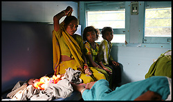 Indian women sit in economy class of a Indian train with their children while traveling from Agra to Delhi, India. Photo By Andrew Parsons/ i-Images
