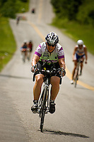 JEROME A. POLLOS/Press..Celeste Burr, from Marietta, Ga., pedals her way up one of the hill climbs near Hayden Lake during the 112-mile bike ride Sunday during the Ford Ironman Coeur d'Alene.