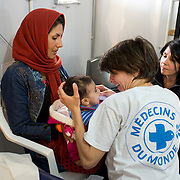 Greece with Doctors of the World (Medecins du monde). Chios Island, one of the places where refugees from Turkey land en route to Northern Europe. Souda camp. Dr Sophie Quinney examines baby Sabina with help of translator Simi (?)