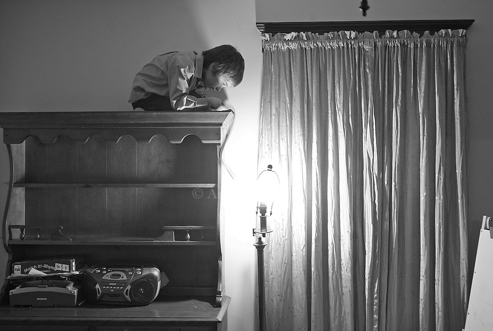 Aidan Sumner, 4, who has both autism and lead poisoning, stares at a bare lightbulb from his perch atop a bookcase,  February 12, 2008.    Aidan loves heights and takes every opportunity to climb.