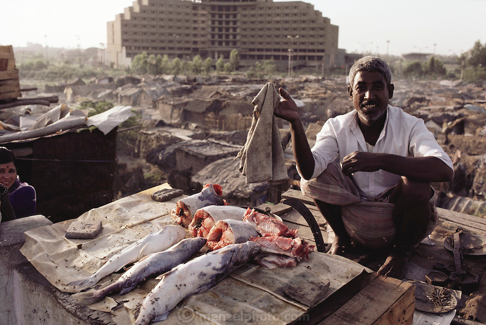 Fish vendor awaiting customers waves flies away from his wares with a rag in shantytown slum of New Delhi, India.