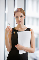 Portrait of confident businesswoman holding documents and eyeglasses in office