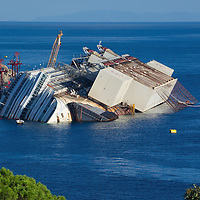 ISOLA DEL GIGLIO, ITALY - SEPTEMBER 14:  The wreckage of the Costa Concordia is seen from above the harbour on September 13, 2013 in Isola del Giglio, Italy. The Costa Concordia is reportedly due to be righted beginning on the morning of September 16, then, if the operation is successful, it will be towed away and scrapped.  (Photo by Marco Secchi/Getty Images)
