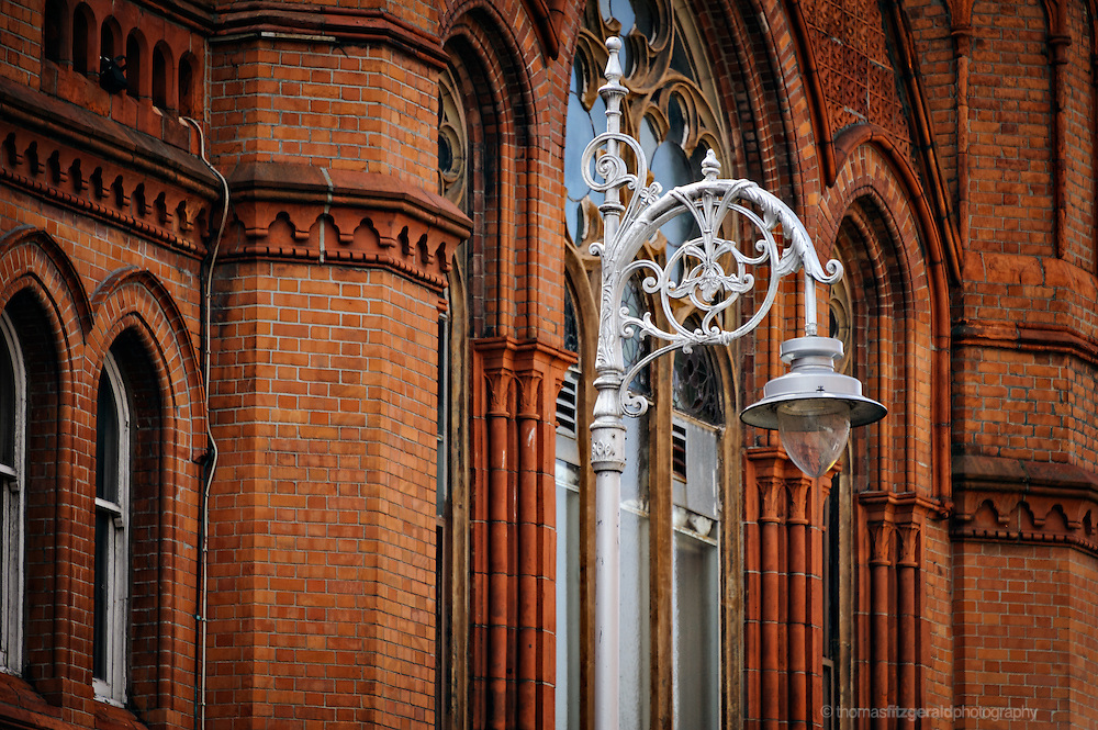 A beautiful iconic Dublin Lamp Post against the back drop of the red bricks of one of Dublin's Victorian era buildings