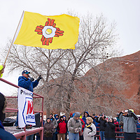 Bill Noe (left) flys the breakfast flag with bacon and eggs making the Zia symbol, while Bill Lee concludes the pilots briefing Saturday Dec. 1, at Red Rock Park in Church Rock. Mass ascensions were canceled Friday through Sunday due to the weather.