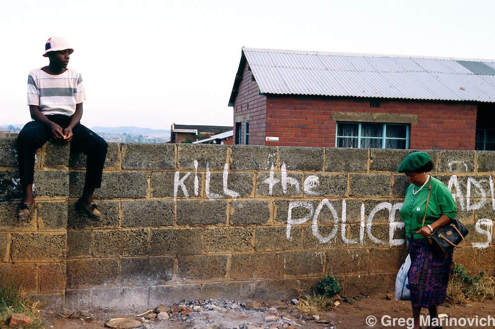 Soweto South Africa 1994. Grafitti reads 'Kill the Police' as a youth sits on a wall and a woman returns from work in Soweto, South Africa, 1994.