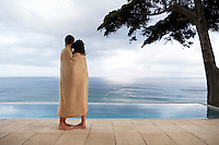 Couple covered in towel standing by infinity pool side view