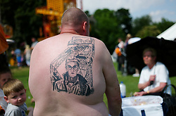"© Licensed to London News Pictures. 13/07/2013<br /> <br /> Durham City, England, United Kingdom<br /> <br /> A former miner shows off his tattoo as he attends the Durham Miners Gala in the City.<br /> <br /> The Durham Miners' Gala is a large annual gathering held each year in the city of Durham. It is associated with the coal mining heritage of the Durham Coalfield, which stretched throughout the traditional County of Durham, and also gives voice to miners' trade unionism. <br /> <br /> Locally called ""The Big Meeting"" or ""Durham Big Meeting"" it consists of banners, each typically accompanied by a brass band, which are marched to the old Racecourse, where political speeches are delivered. In the afternoon a Miners' service is held in Durham Cathedral <br /> <br /> Photo credit : Ian Forsyth/LNP"