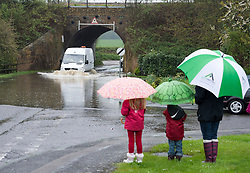 © London News Pictures. 29/04/2012. Ingatestone, UK. A mother and her two children with umbrellas watch a van drive through flood water in the town of Ingateston in Essex on April 29, 2012 . The nearby river Wid broke it's banks following torrential rainfall. Photo credit : Ben Cawthra /LNP