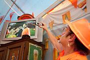 Een vrouw neemt een foto van het televisiescherm als de finale van het WK voetbal tussen Nederland en Spanje van start gaat. In een grote tent aan de Royaards van den Hamkade in de Utrechtse volkswijk Ondiep, de wijk waar Wesley Sneijder vandaan komt, kijkt een grote groep oranjesupporters naar de wedstrijd.<br /> <br /> A woman is taking a picture of the Dutch soccer players on a tv screen at the start of the finals of the World Championship soccer 2010.