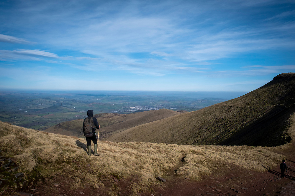 A child with a rucksack and walking stick stands admiring the landscape view from Pen Y Fan mountain range in Brecon Beacons National Park, Wales, Powys, United Kingdom.  Pen Y Fan is the highest point in the Brecon Beacons hill and mountain range in South Wales. The National Park was established in 1957 due to the spectacular landscape which is rich in natural beauty and is run by the National Trust.  (photo by Andrew Aitchison / In pictures via Getty Images)