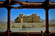 Arkansas Democrat-Gazette/BENJAMIN KRAIN 10-19-03<br /> A bombed out bus window frames the war ravaged Darulaman Palace in Kabul as horse draw carriage passes by.  The former presidential palace has become a symbol of the relentless battle among Islamic factions for control of the Afghan capital during the county's civil wars of the early 1990s.
