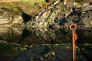 """Detail featuring rusty safety chain at the Bogey Hole, Newcastle Australia. The Bogey Hole is a popular swimming spot near King Edward Park, Newcastle Australia. It was constructed by order of Commandant Morisset in about 1820 for his own personal use. The name """"Bogey Hole"""" comes from the Aboriginal word meaning """"to bathe""""."""